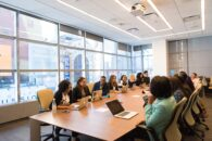 group of people sitting around a large conference room in a commercial office building